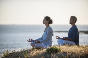 handsome couple practicing meditation exercises on the beach at sunset